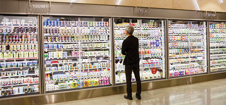 Man looks at milk and other grocery items in a refrigerator in a store.