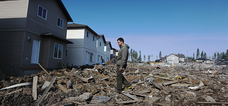 Man walks through rubble of a house in aftermath of a wildfire.