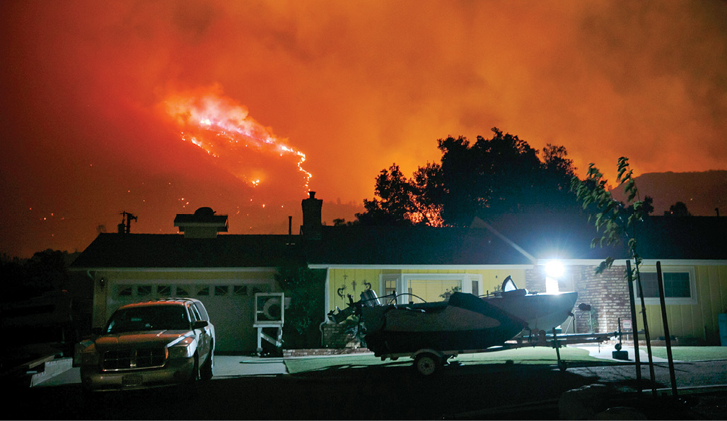 A 2016 wildfire menaces property in California.