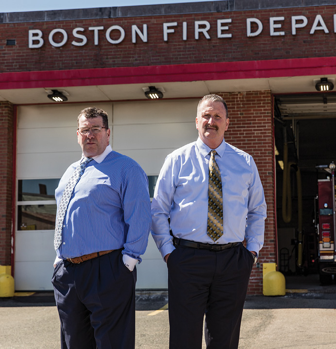 Joe Finn and Richie Paris stand outside a Boston firehouse