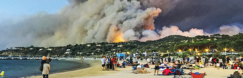 Beach goers look at a raging wildfire in the distant hills.